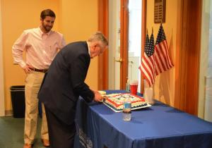 Russ Furnas, WWII vet, cutting the cake after sharing his story to the Gainesville Chamber staff